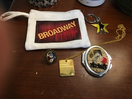 Broadway canvas pouch, Phantom of the Opera hand mirror, Les Miserables adjustable plastic ring, Wicked necklace, and Hamilton Key Chain