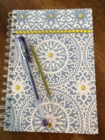 Lined journal with purple pen and gold ink replacement